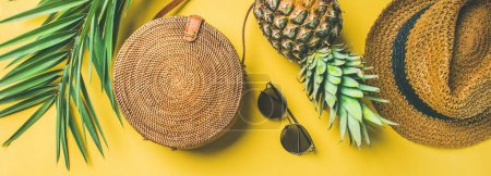 Photo for Colorful summer female fashion outfit. Straw hat, bamboo bag, sunglasses, palm branches, pineapple over yellow background - Royalty Free Image
