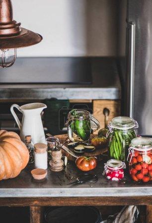 Photo pour Décapage et mise en conserve des légumes d'automne. Ingrédients pour la cuisson et pots de verre avec conserves maison de légumes sur le comptoir de cuisine en bois, gros plan. Concept d'aliments fermentés organiques sains - image libre de droit
