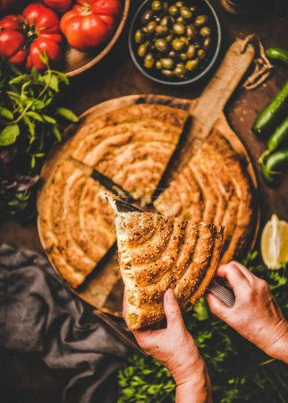 Photo pour Turkish traditional pastry for breakfast. Human hands holding piece of borek pie with spinach filling and vegetable ingredients over rusty table background, top view. Turkish traditional cuisine - image libre de droit
