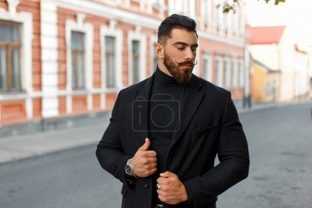Fashionable man with a hairdo in a stylish black coat posing on the street