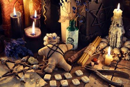 Photo pour Poupée vaudou, bougies noires, pentagram et des livres sur la table de la sorcière. Occulte, ésotérisme, divination et wicca concept. Arrière-plan mystique et vintage - image libre de droit