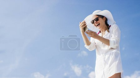 Young fashionable woman using her phone on a beautiful day