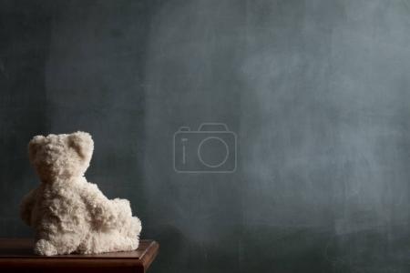 Blackboard background. Green board. A Teddy Bear on a table.