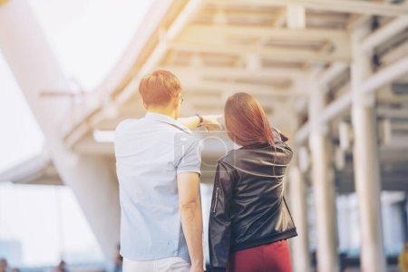 Photo pour Retour de Couple Homme Femme voyageur avec valise sur fond de bâtiment du centre d'affaires. - image libre de droit