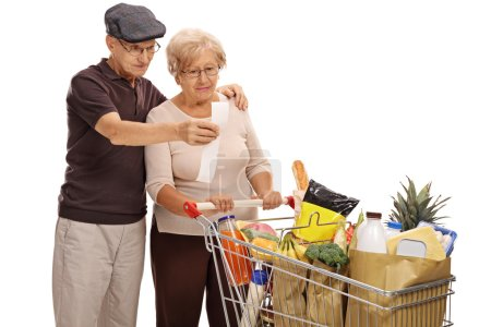 Shocked elderly couple looking at a store receipt