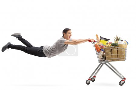 Man being pulled by a shopping cart full of groceries