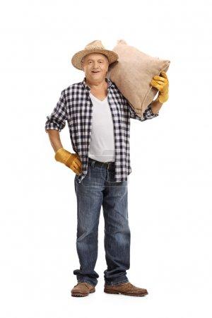 Mature farmer holding a burlap sack