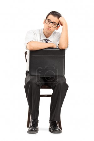 Sad businessman with suitcase waiting for job interview