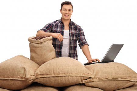 Photo for Young agricultural worker posing with burlap sacks filled with coffee beans and a laptop isolated on white background - Royalty Free Image