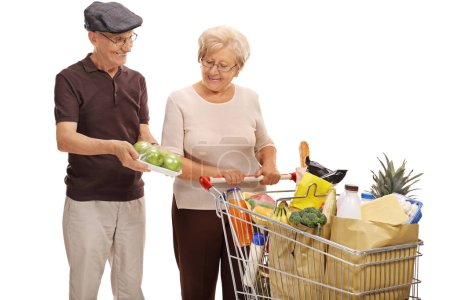 Man showing pack of apples to woman with shopping cart