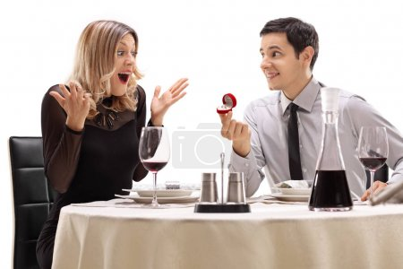 guy proposing to his girlfriend at a restaurant table