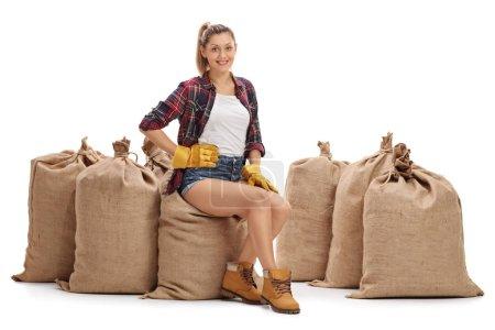 Agricultrice, assis sur un tas de sacs de toile de jute