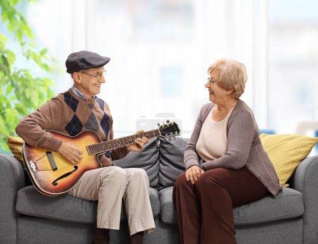Elderly man playing a guitar to an elderly