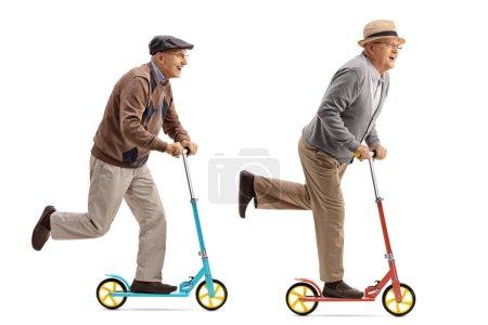 Foto de Perfil de longitud completa la foto de dos hombres ancianos alegres montar scooters aislados sobre fondo blanco - Imagen libre de derechos