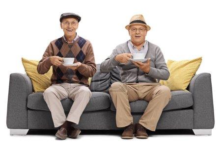Joyful seniors with cups sitting on a sofa