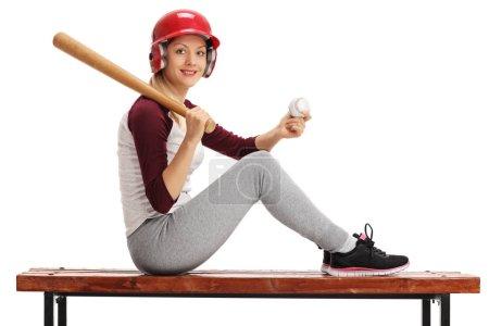 Foto de Mujer joven posando con una pelota de béisbol y un bate en un banco de madera aislado sobre fondo blanco - Imagen libre de derechos