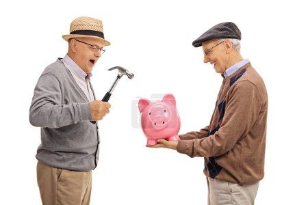 men preparing to break a piggybank with a hammer