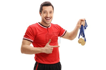 football player holding gold medals and pointing