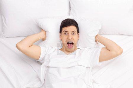 Photo for Man lying in bed and screaming - Royalty Free Image