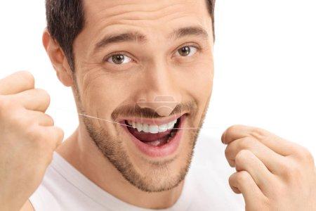 Photo pour Homme soie dentaire ses dents isolées sur fond blanc - image libre de droit