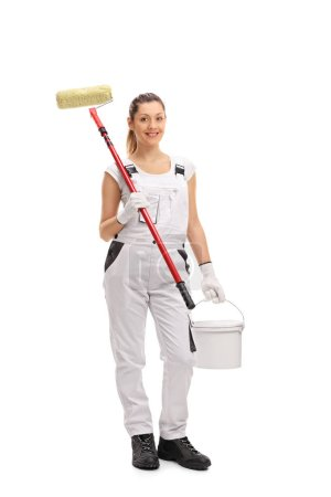female painter holding paint roller and color bucket