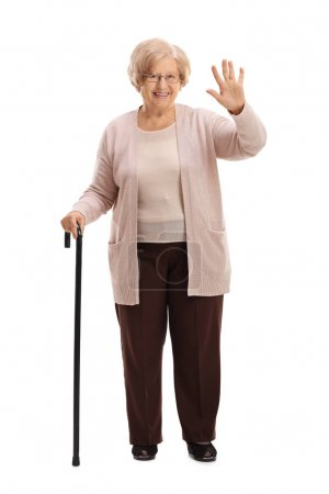 Photo for Full length portrait of an elderly woman with a walking cane waving isolated on white background - Royalty Free Image
