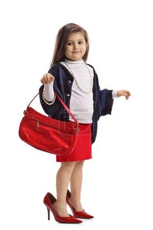 Photo pour Portrait de toute la longueur d'une petite fille en talons surdimensionnés, tenant un sac isolé sur fond blanc - image libre de droit