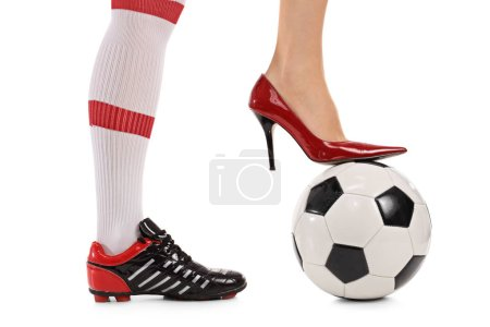Soccer shoe and high-heeled shoe pressing a football