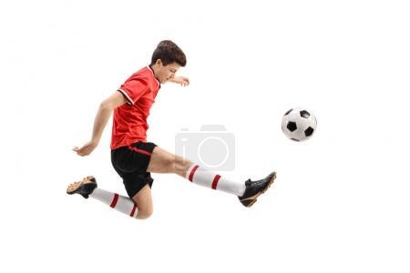 Teenage soccer player kicking a football