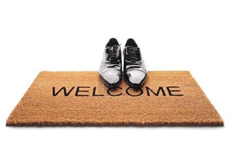 Photo pour Paire de chaussures sur un paillasson avec le mot Bienvenue écrit dessus isolé sur fond blanc - image libre de droit