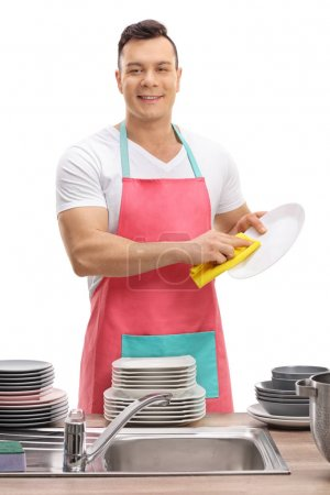 Young guy in an apron wiping dishes