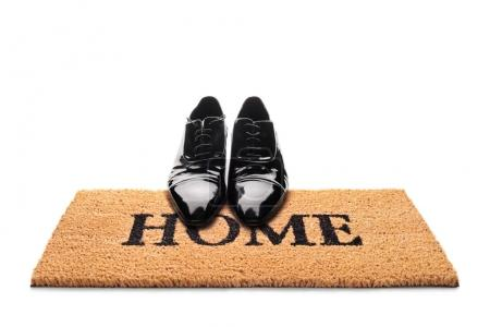 Pair of shoes on a doormat with the word home