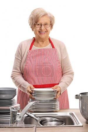 mature woman with a stack of clean plates