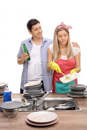 Man with beer hugging his wife doing the dishes