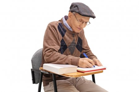 Elderly student sitting in a school chair and taking notes