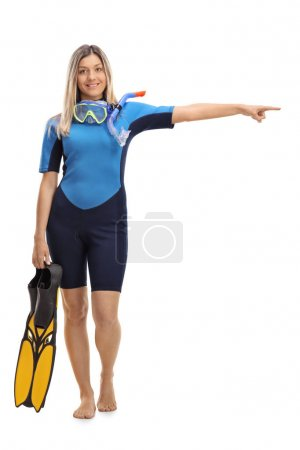 Woman in a wetsuit with snorkeling equipment pointing right