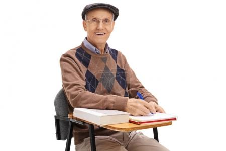 Photo for Elderly student in a school chair taking notes and looking at the camera isolated on white background - Royalty Free Image