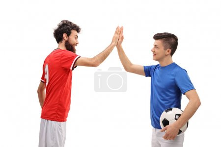 Father and son dressed in sport jerseys high fiving
