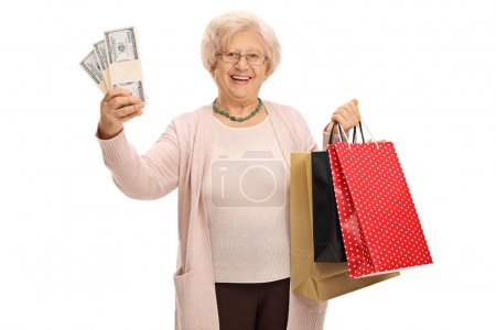 elderly woman holding stacks of money and shopping bags