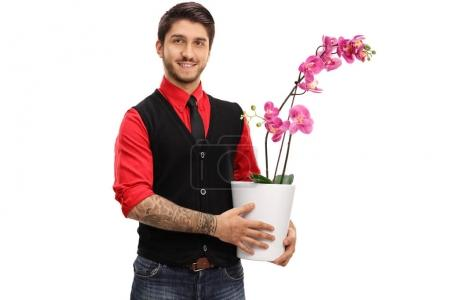Tattooed guy holding an orchid flower in a pot
