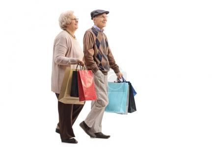 Senior couple with shopping bags walking