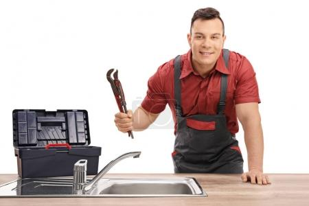 Plumber with a pipe wrench and a toolbox