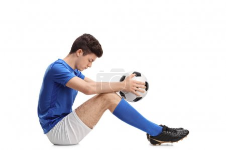 Photo for Depressed teenage football player sitting on the floor isolated on white background - Royalty Free Image