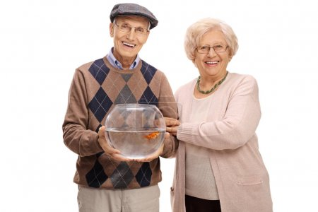 Joyful mature couple with a goldfish in a bowl