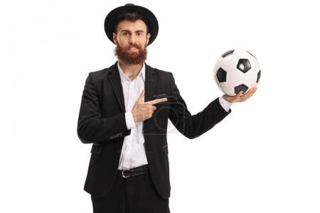 Bearded guy holding a football and pointing