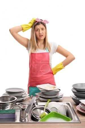 woman behind a sink filled with dirty plates