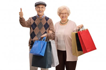 man and woman with shopping bags making thumb up
