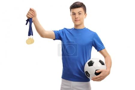 Teenage soccer player with gold medals and a football