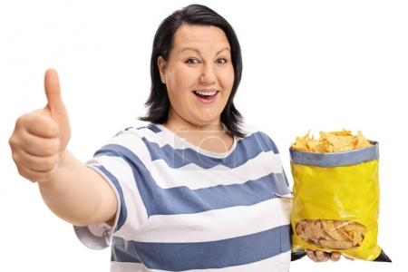 woman with bag of chips making thumb up sign