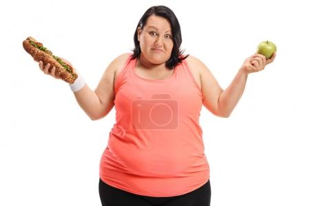 overweight woman holding a sandwich and an apple